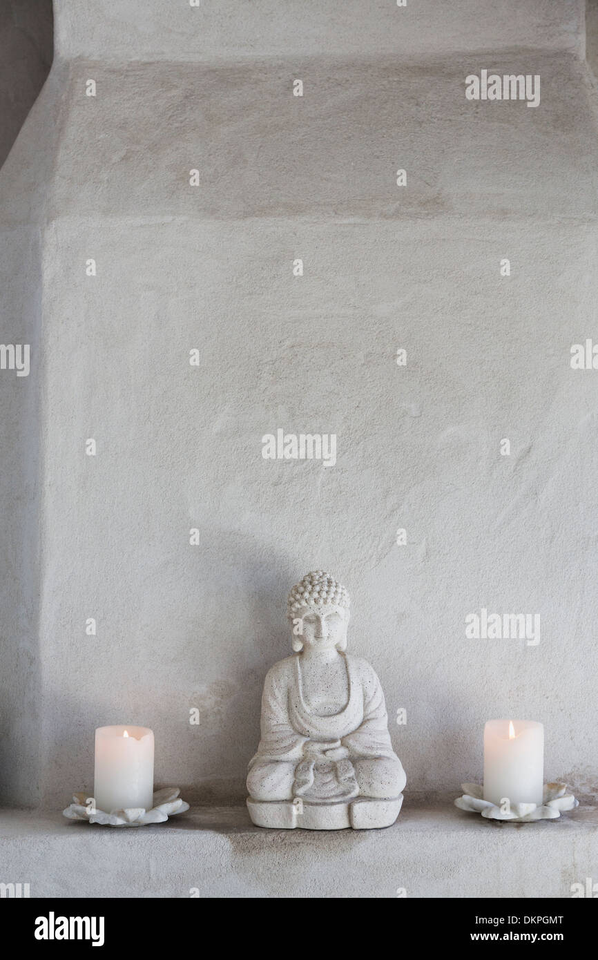 Buddha figurine and candles on ledge - Stock Image