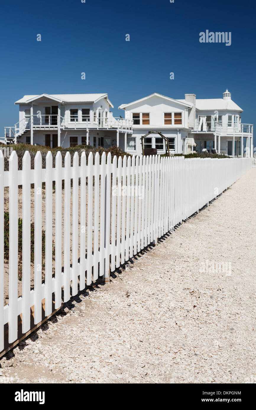 White picket fence leading to beach houses - Stock Image