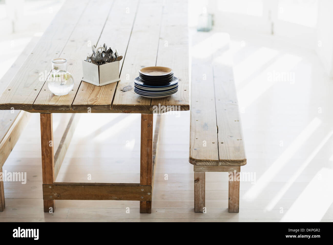Plates and silverware stacked on wooden table - Stock Image
