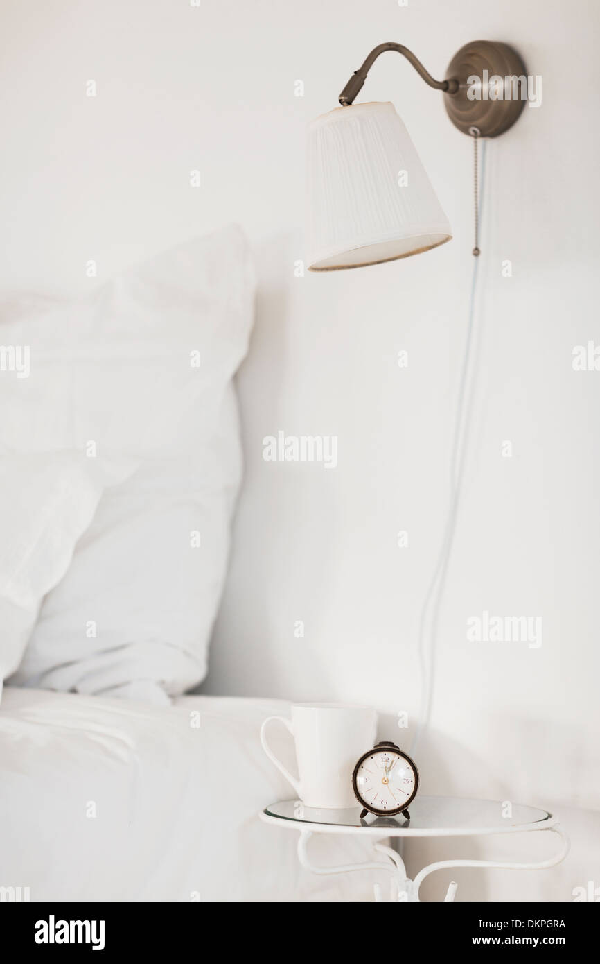 Lamp and bedside table in white bedroom - Stock Image