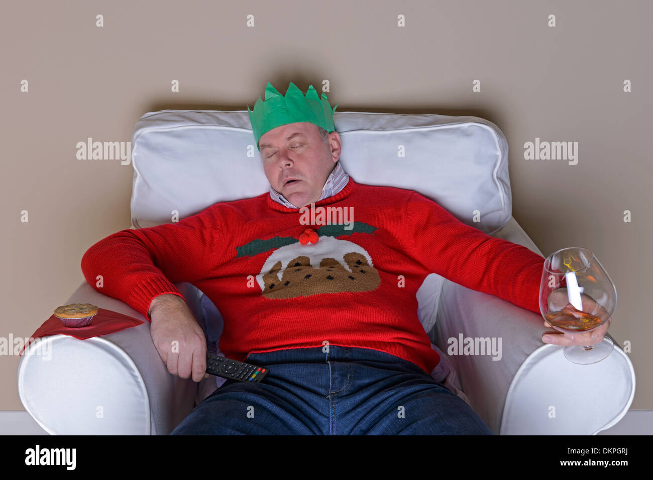 A Christmas tradition - Dad has fallen asleep in an armchair after dinner in front of the TV - Stock Image