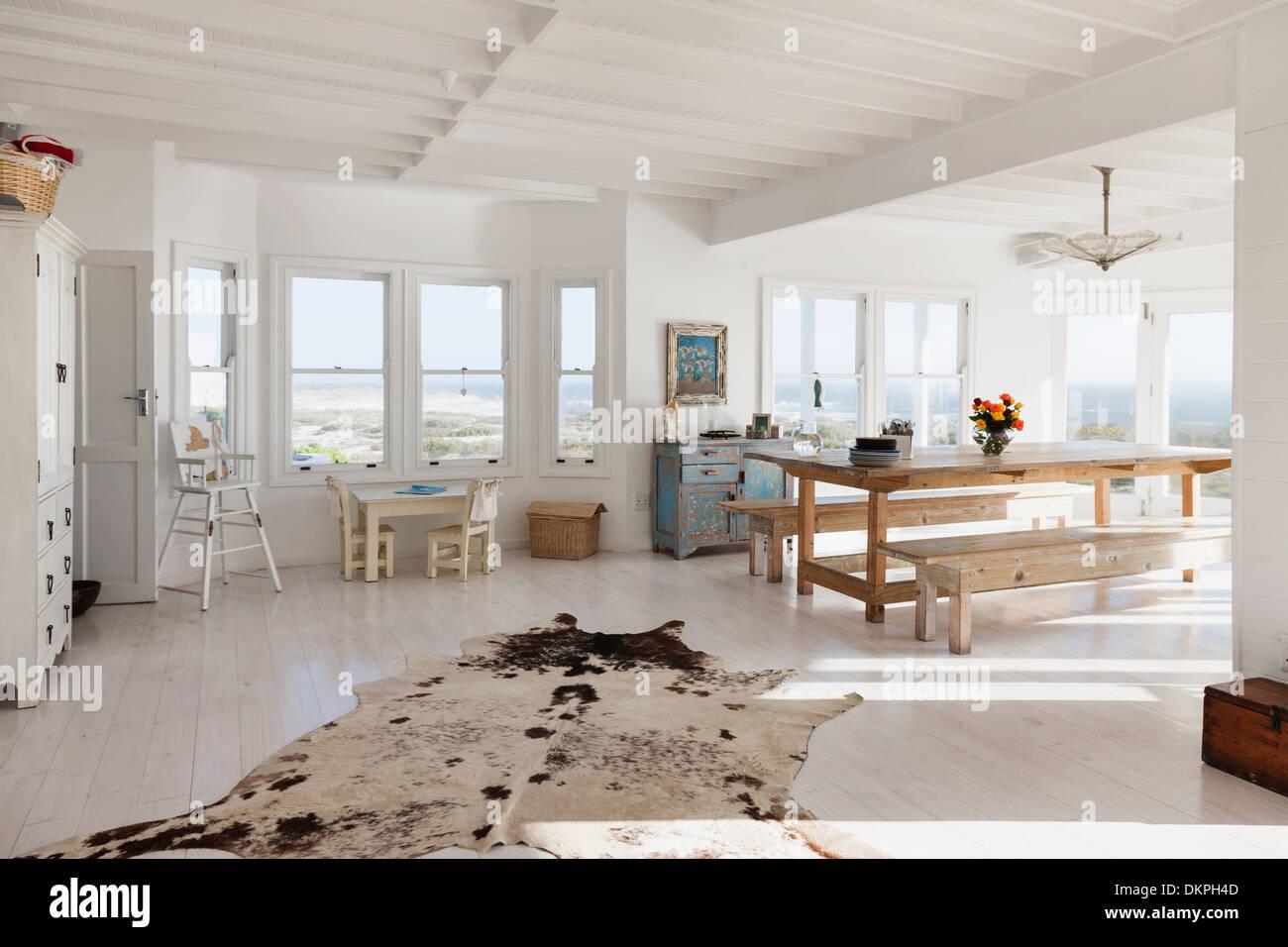 Animal skin rug in sunny dining room - Stock Image