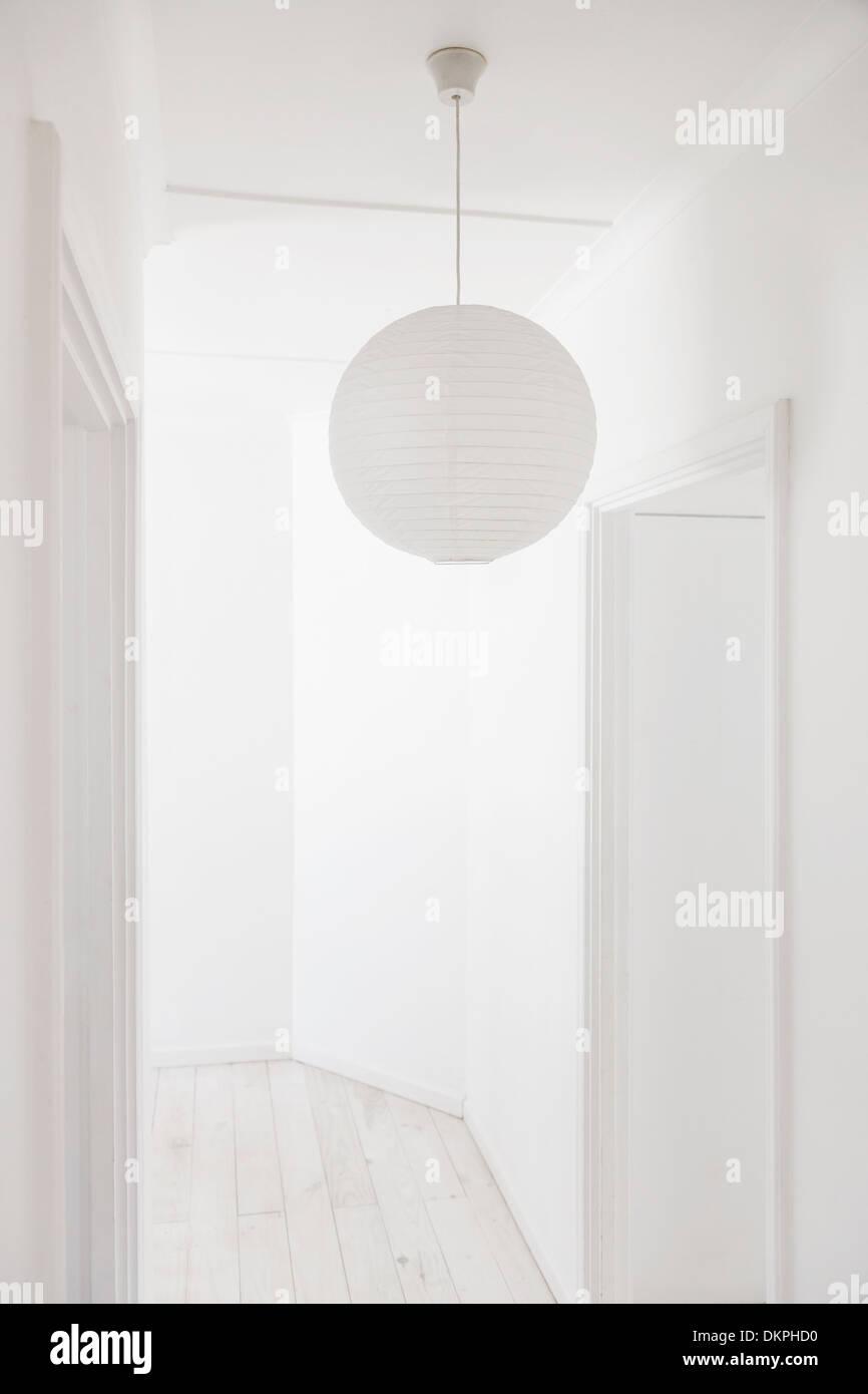 Paper lantern in white corridor - Stock Image