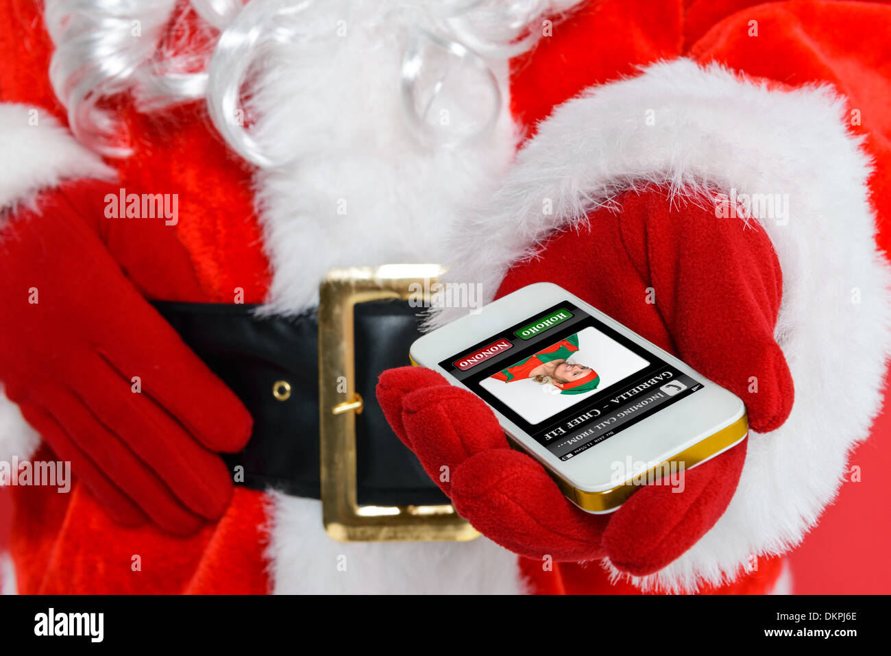 Santa Claus or Father Christmas getting a phone call from his Chief Elf on Christmas Eve. - Stock Image
