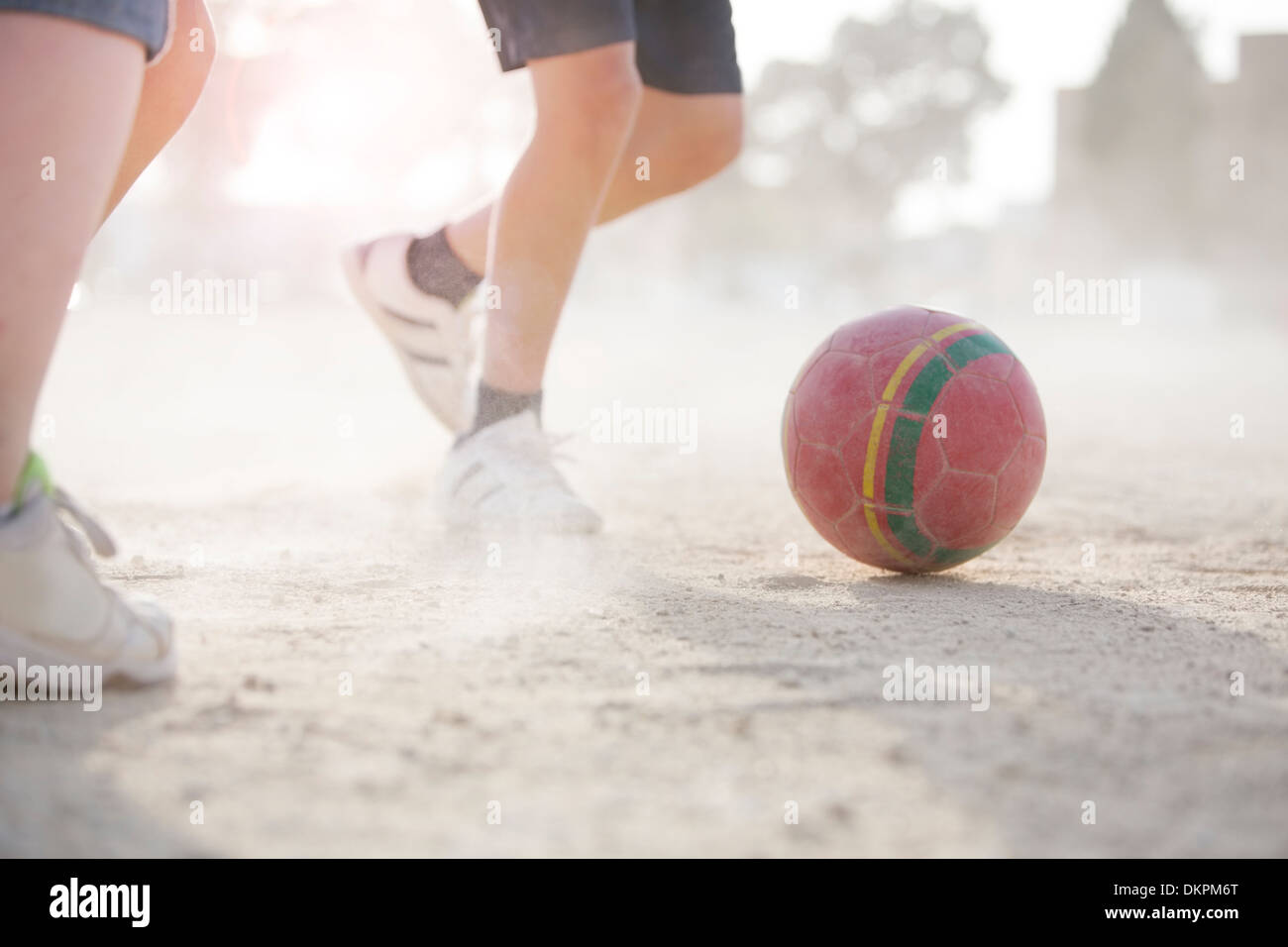 Children playing with soccer ball in sand Stock Photo