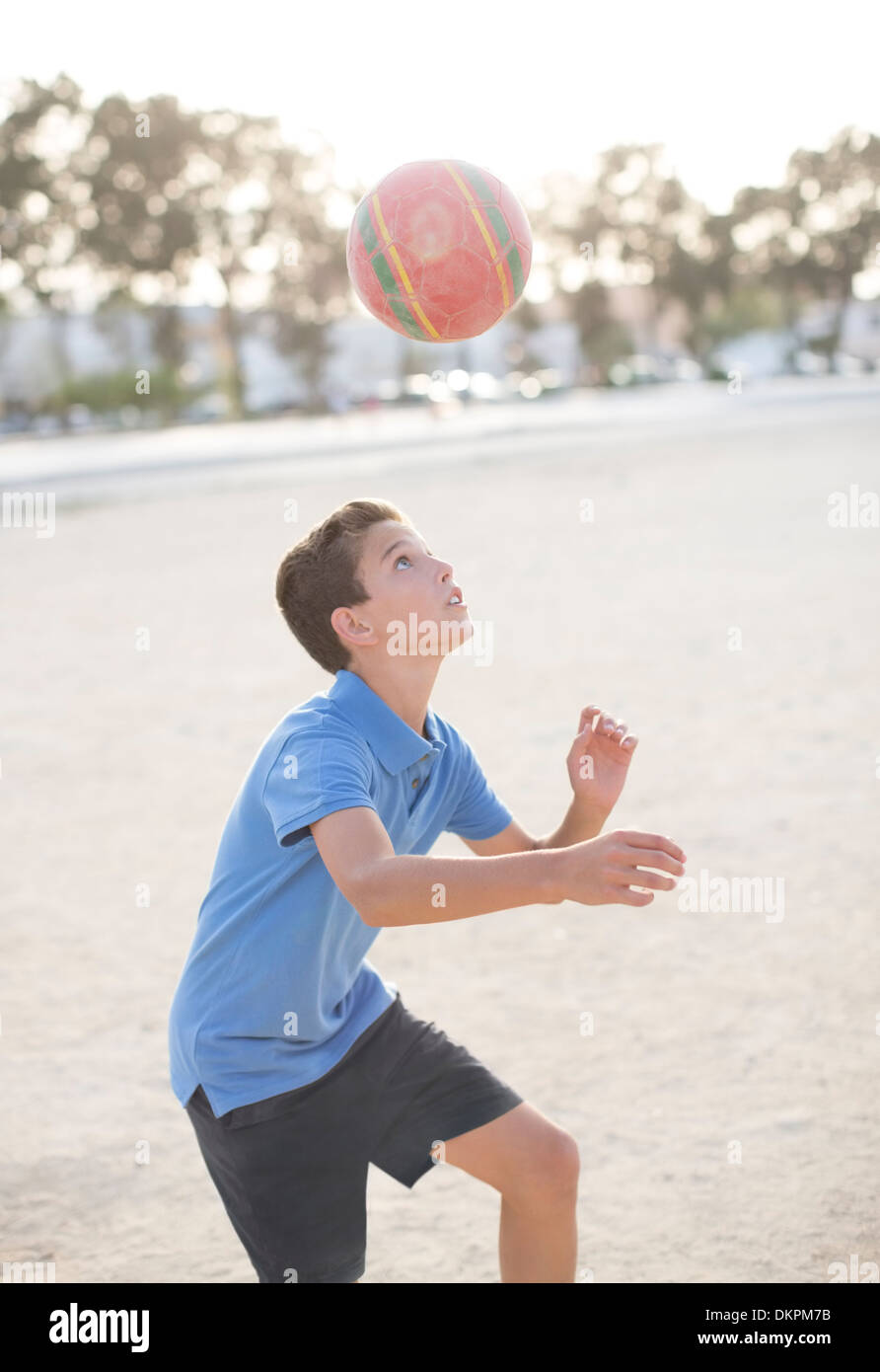 Boy heading soccer ball - Stock Image