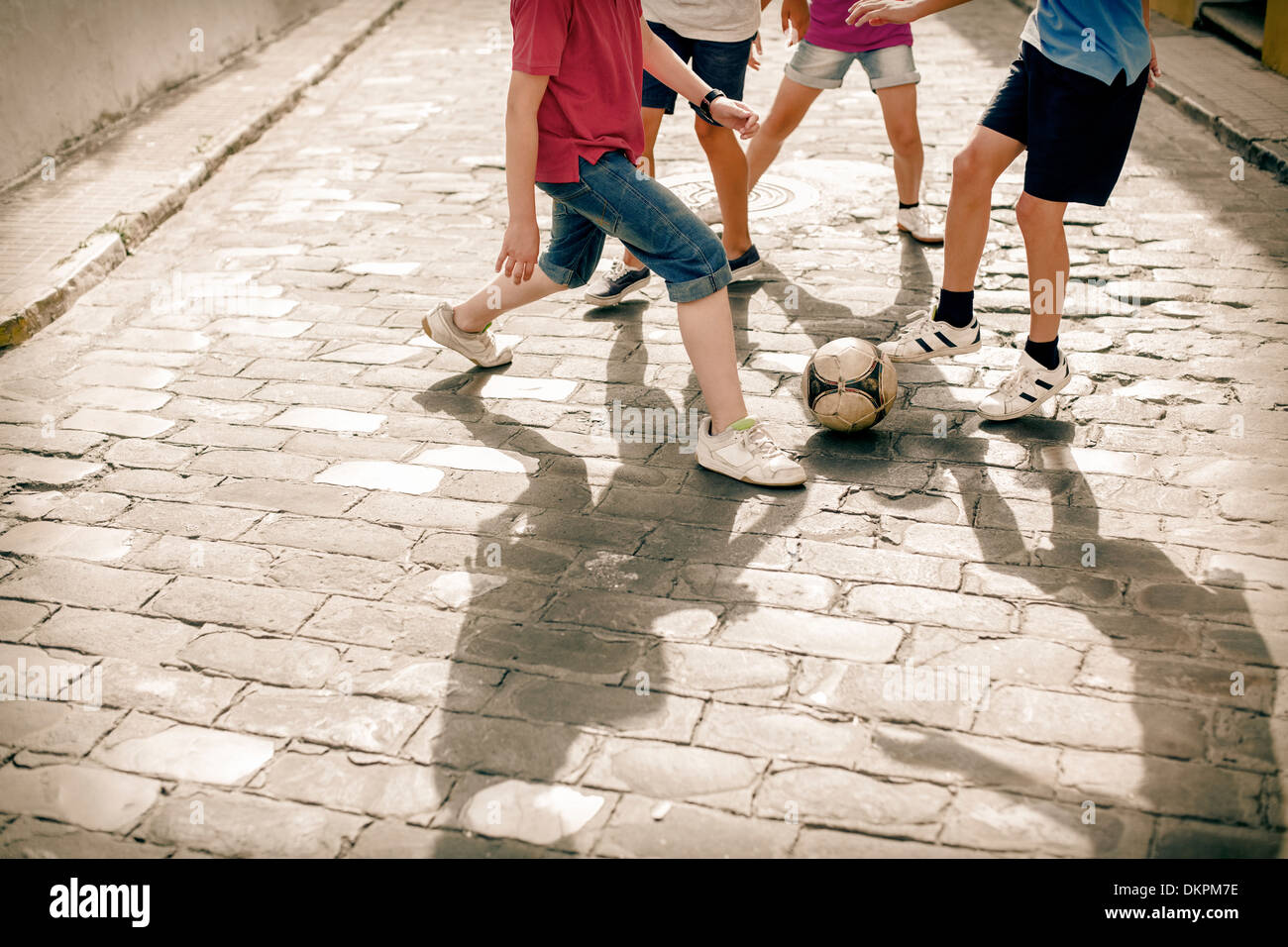 Children playing with soccer ball on cobblestone street - Stock Image