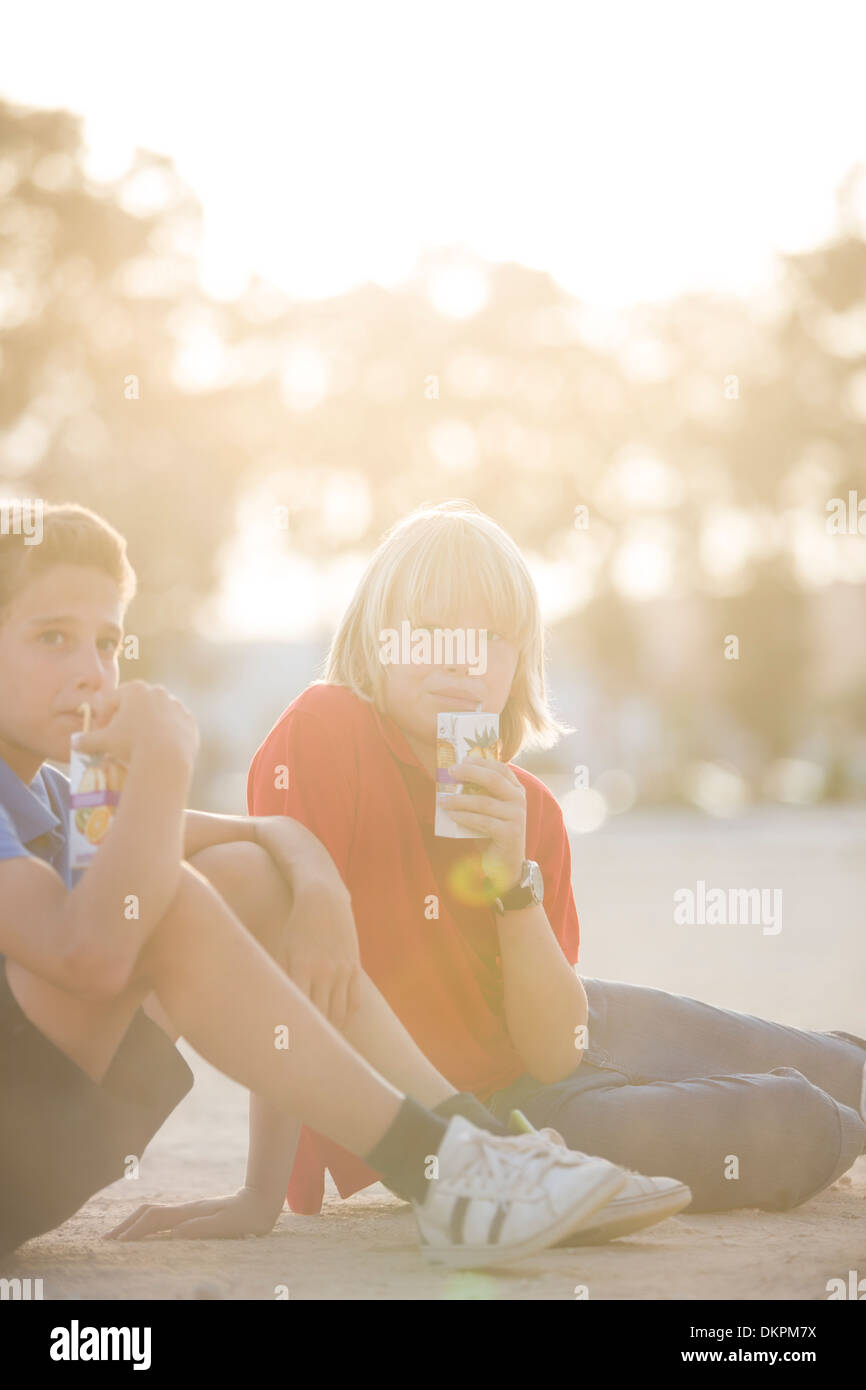 Boys drinking juice outdoors - Stock Image