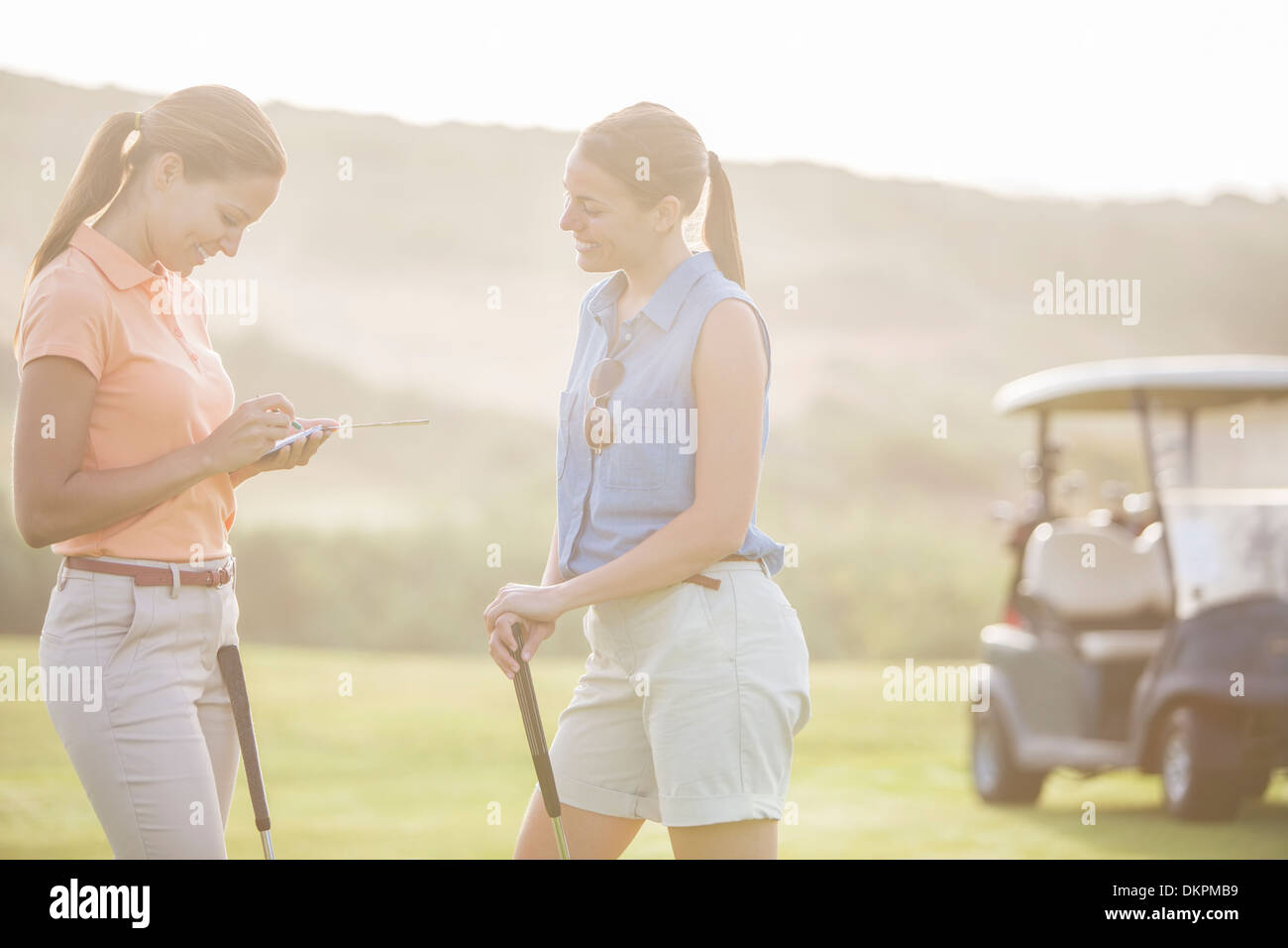 Women playing golf on course - Stock Image
