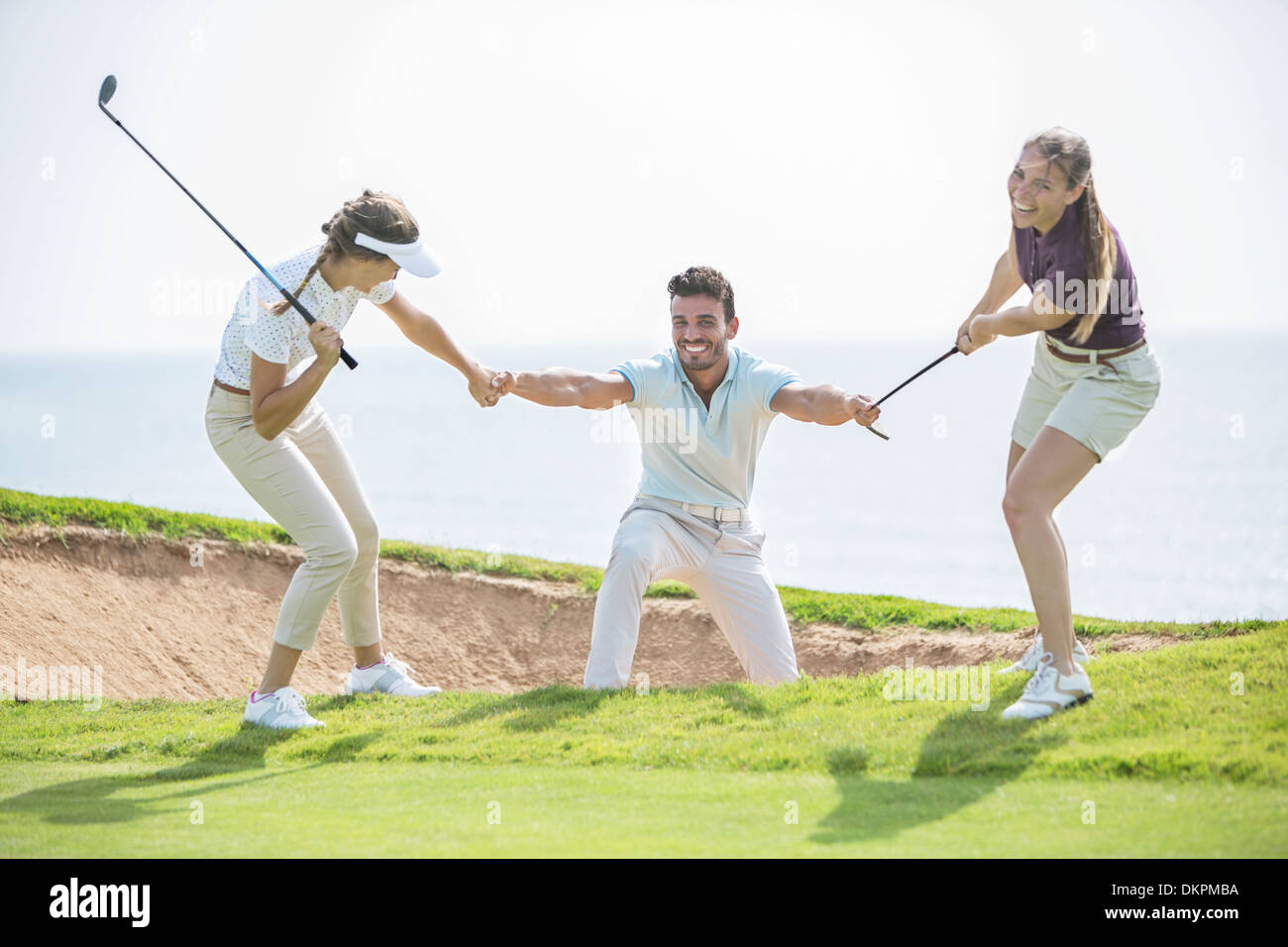 Women pulling man out of sand trap on golf course - Stock Image