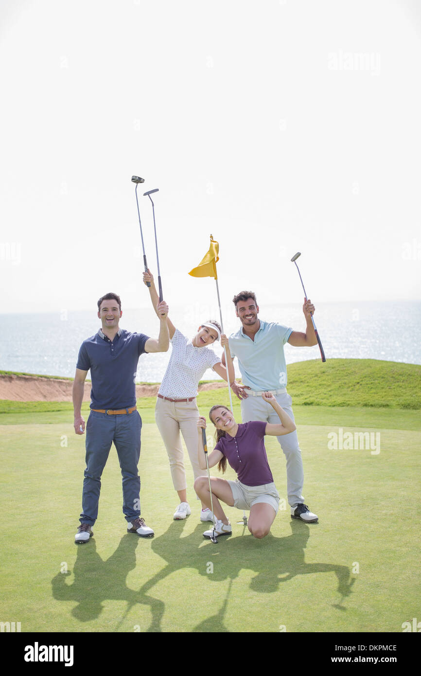 Playful friends on golf course - Stock Image