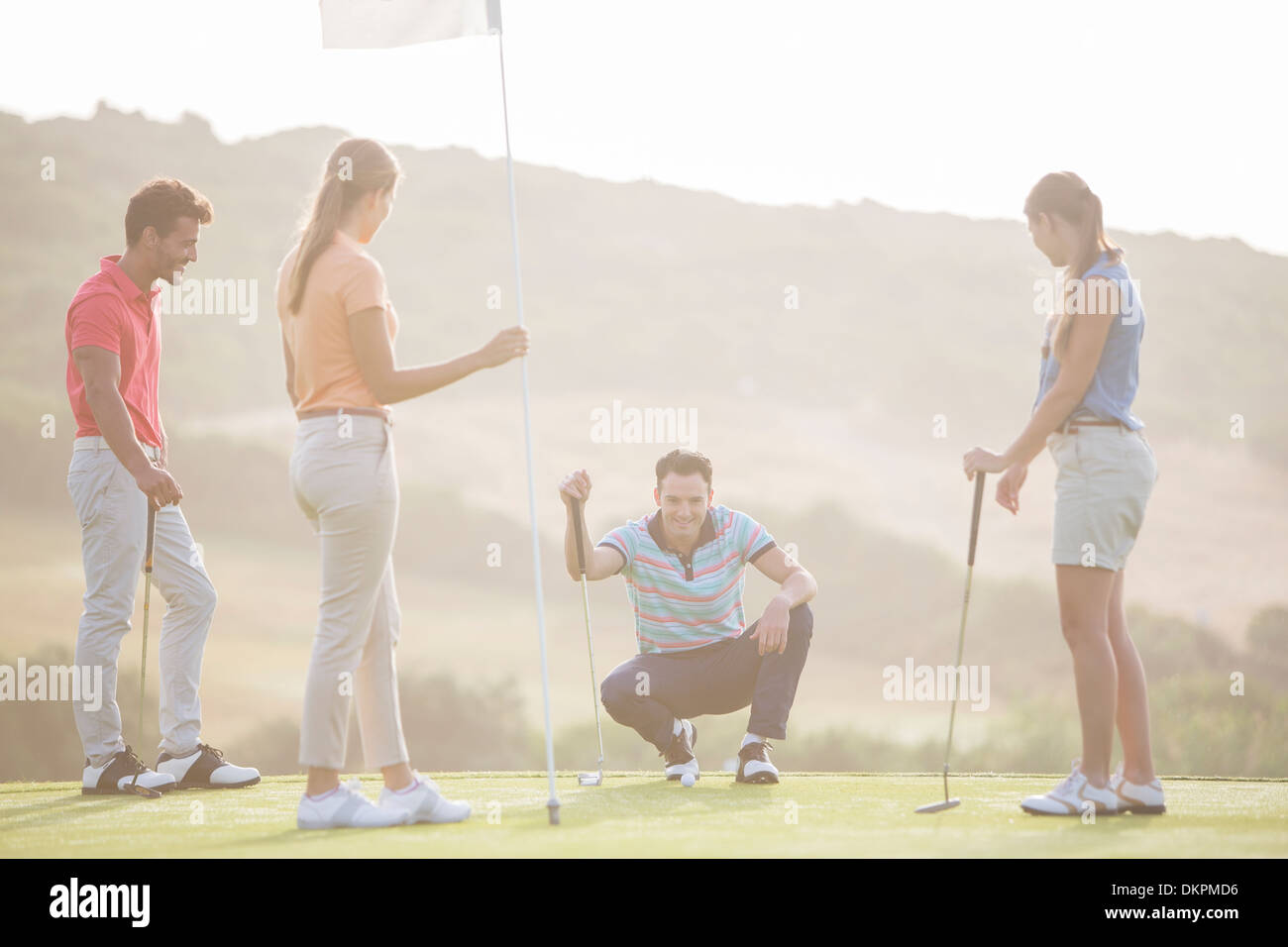 Friends watching man prepare to putt on golf course - Stock Image