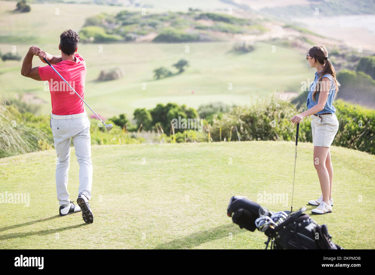 Couple teeing off on golf course - Stock Image