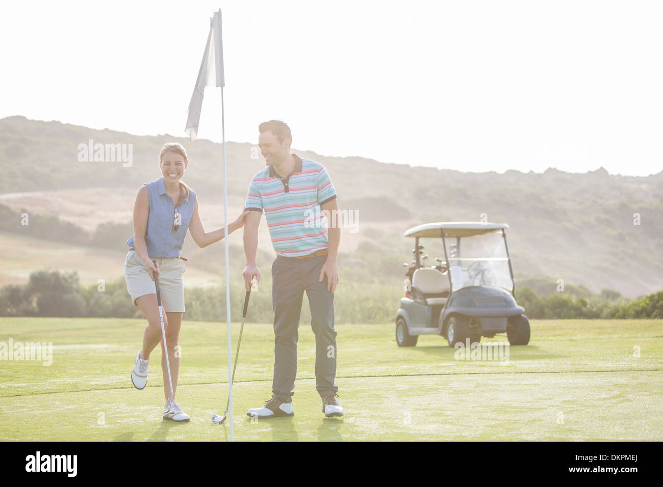 Couple playing golf on course - Stock Image