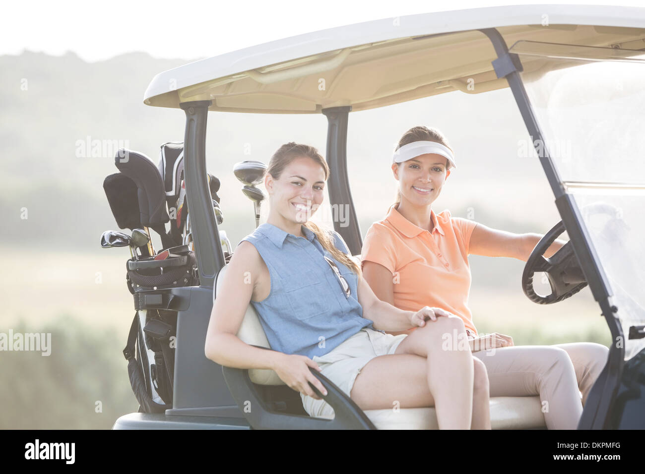 Women driving golf cart on course - Stock Image