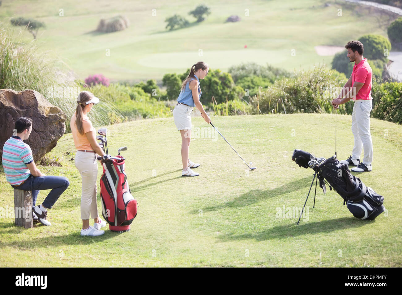 Friends watching woman teeing off on golf course - Stock Image