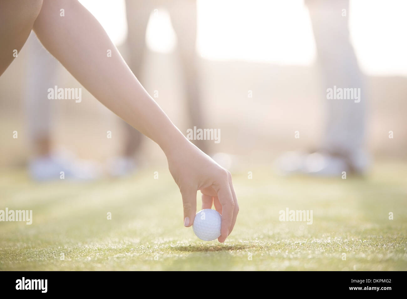 Woman teeing golf ball on course - Stock Image