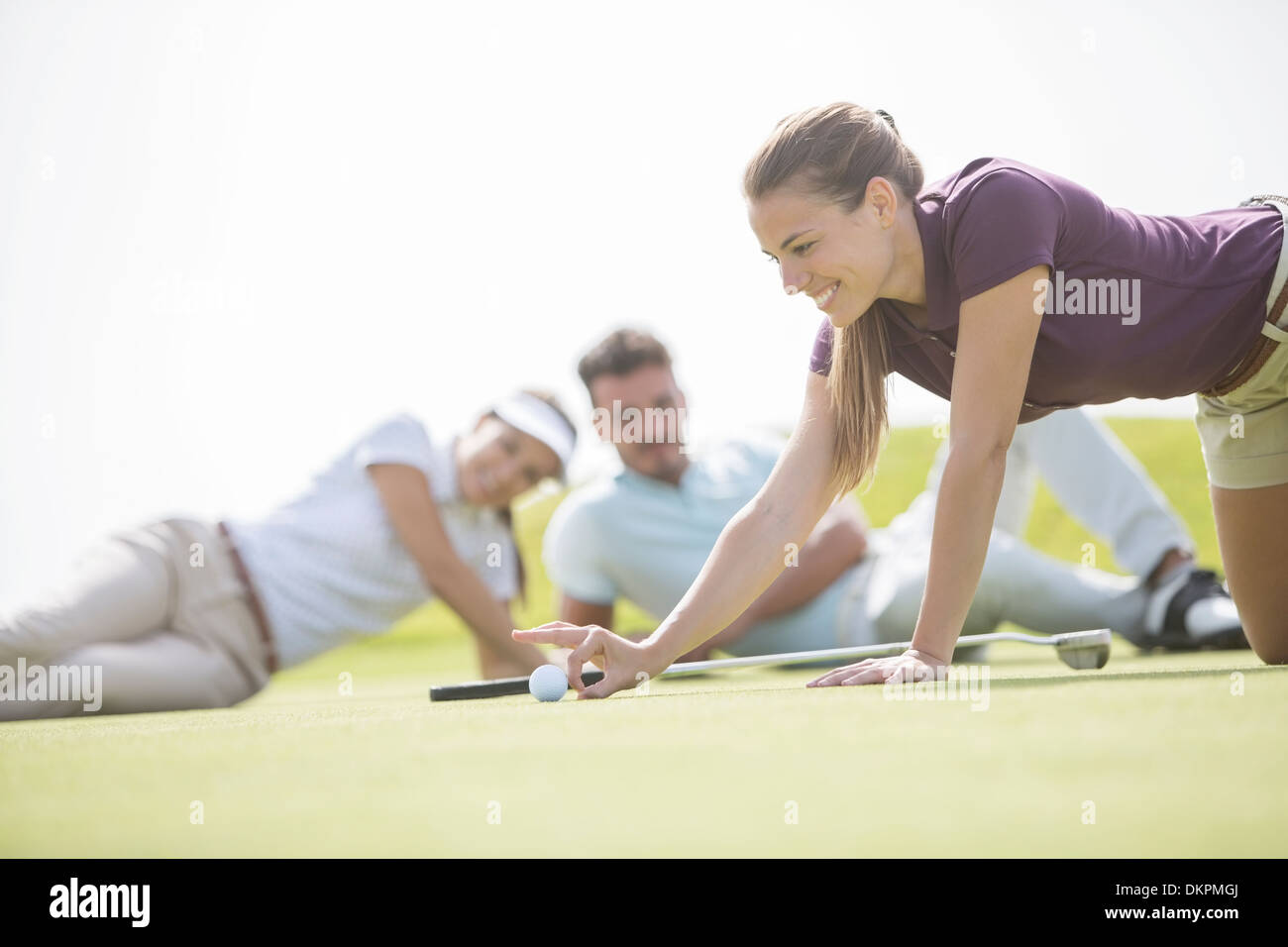 Friends watching woman flick golf ball toward hole - Stock Image