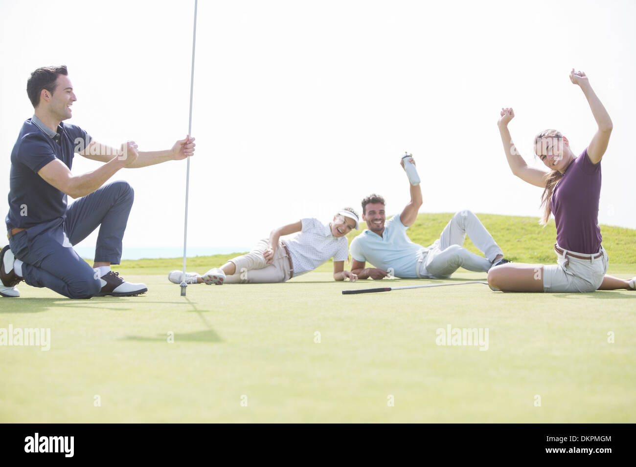 Friends cheering near hole on golf course - Stock Image