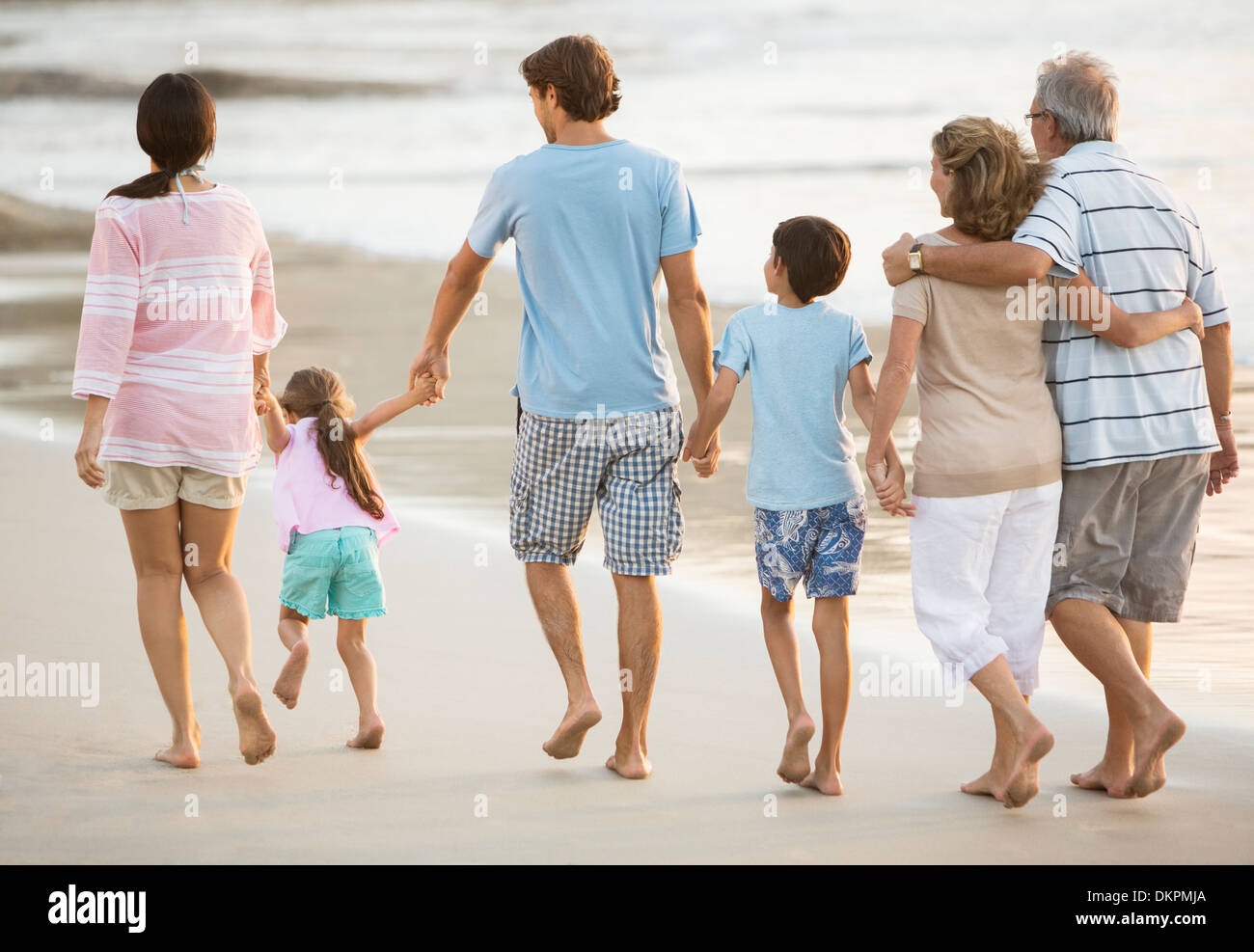 Multi-generation family holding hands on beach - Stock Image