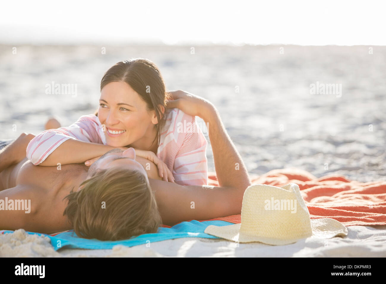 Couple relaxing together on beach - Stock Image
