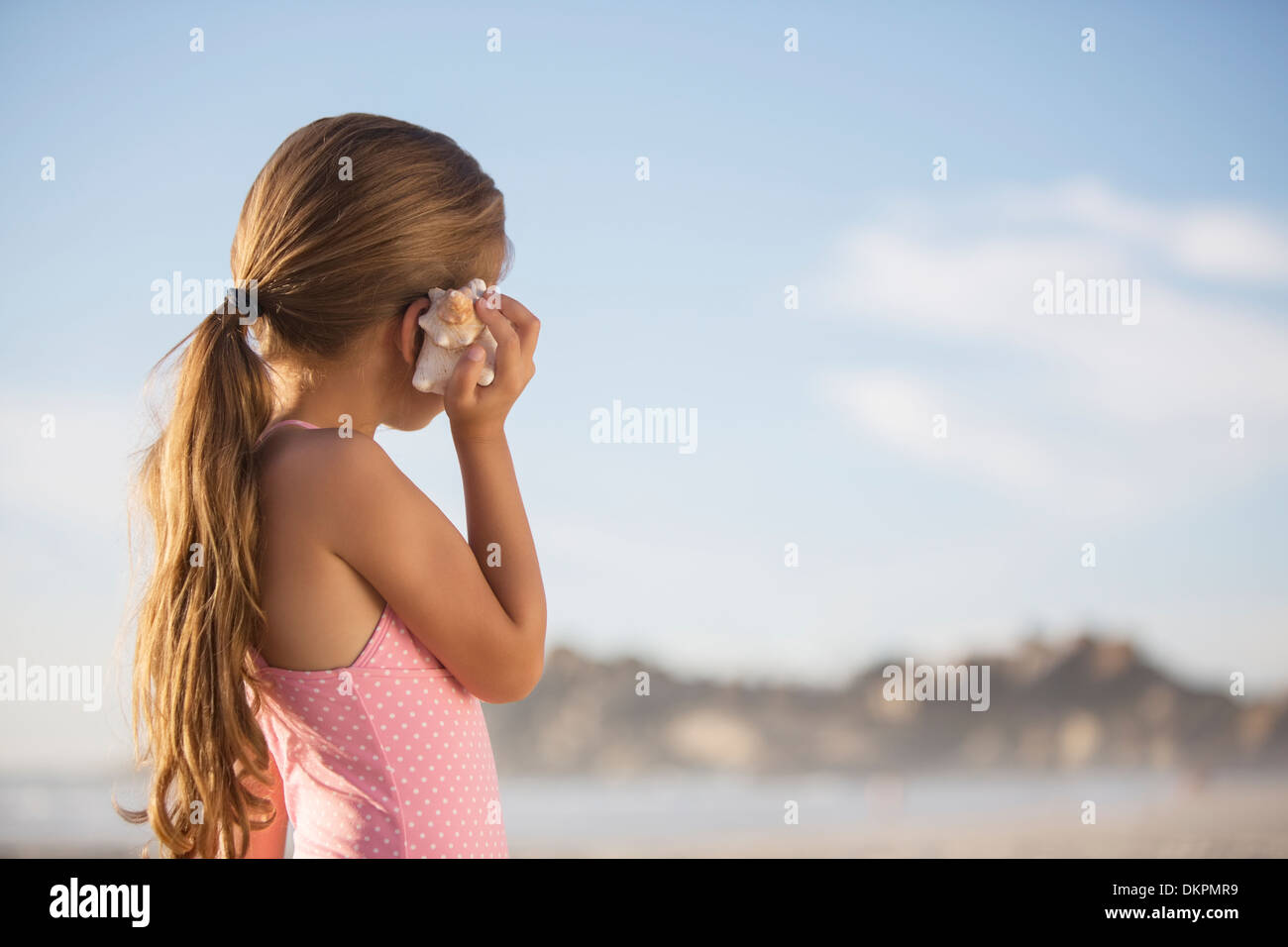 Girl listening to seashell on beach - Stock Image