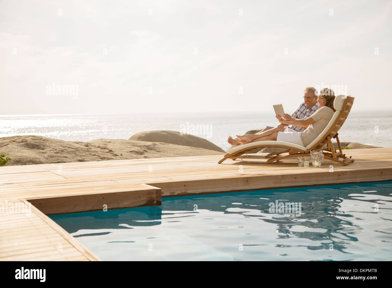 Older couple relaxing by pool - Stock Image