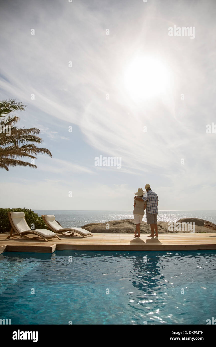 Older couple hugging by pool - Stock Image