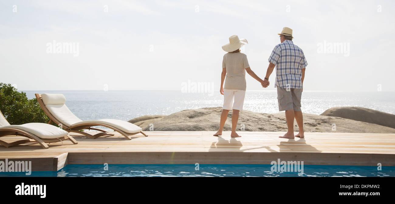 Older couple overlooking ocean from balcony - Stock Image