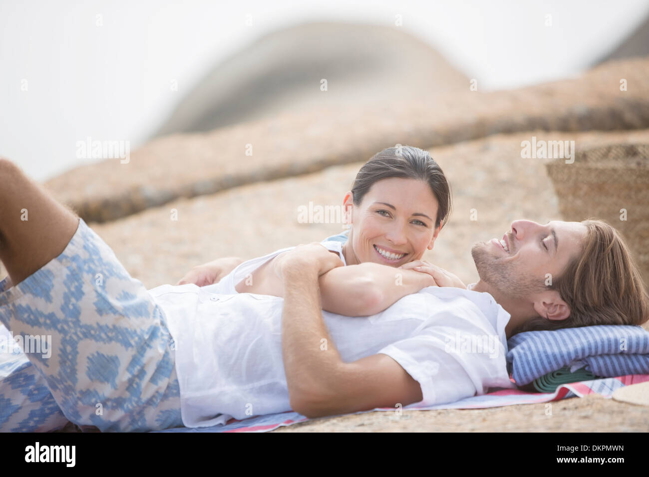 Couple relaxing on beach together - Stock Image