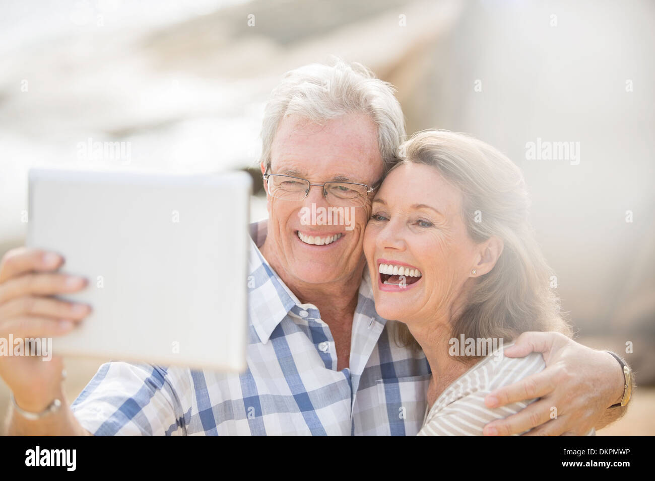 Older couple taking pictures with digital tablet - Stock Image