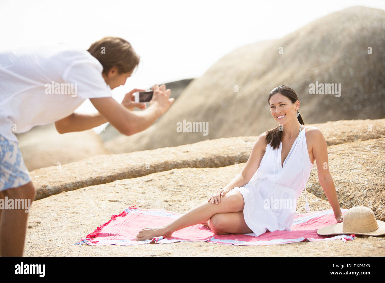 Man taking picture of girlfriend on beach - Stock Image
