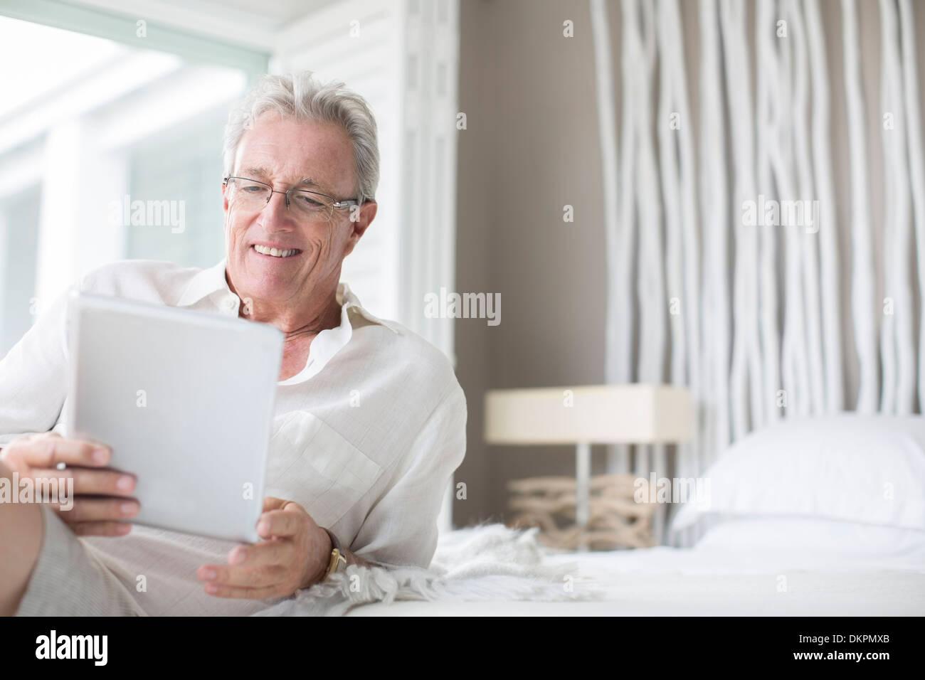 Older man using digital tablet on bed - Stock Image
