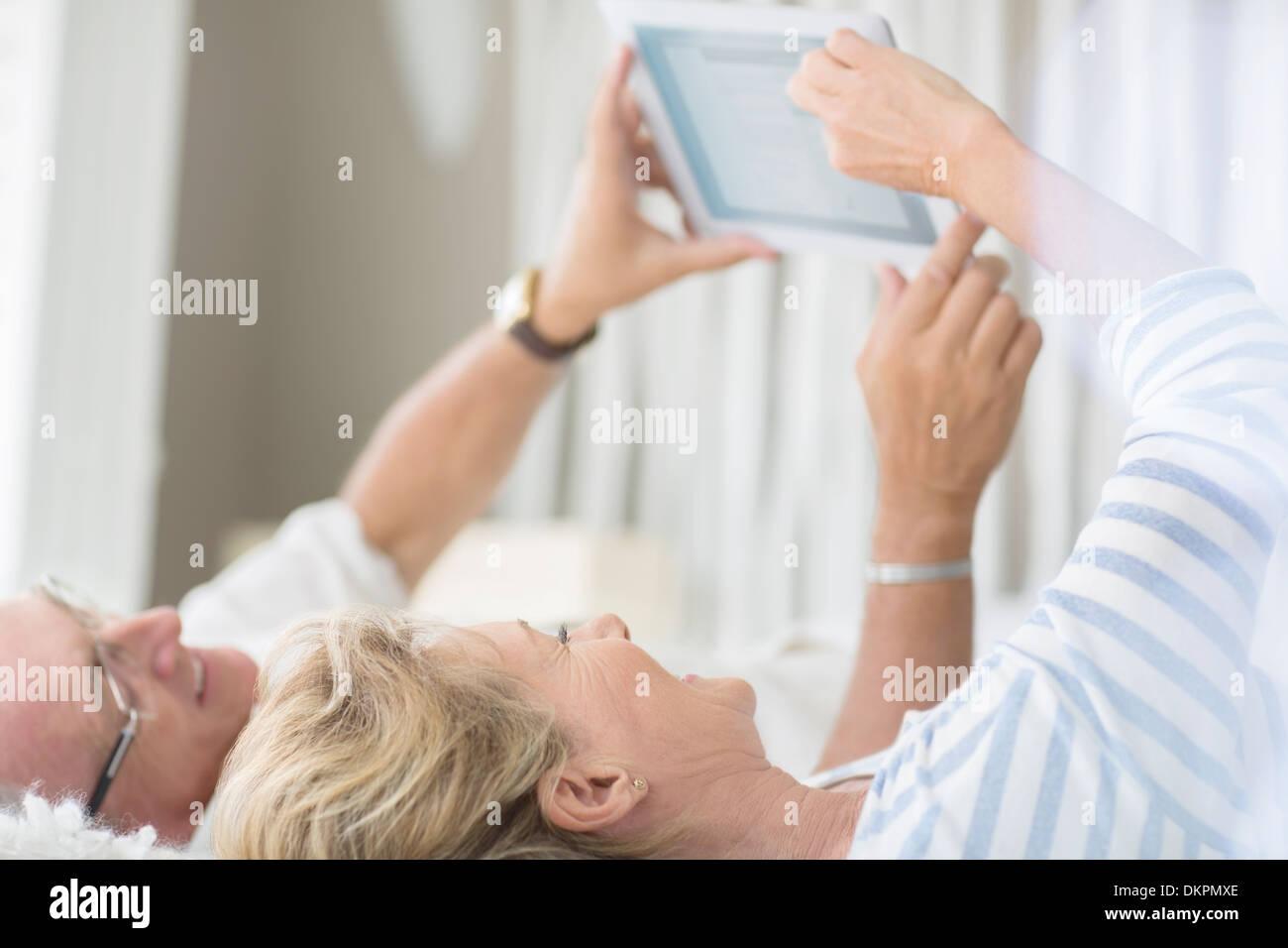 Older couple using digital tablet on bed - Stock Image