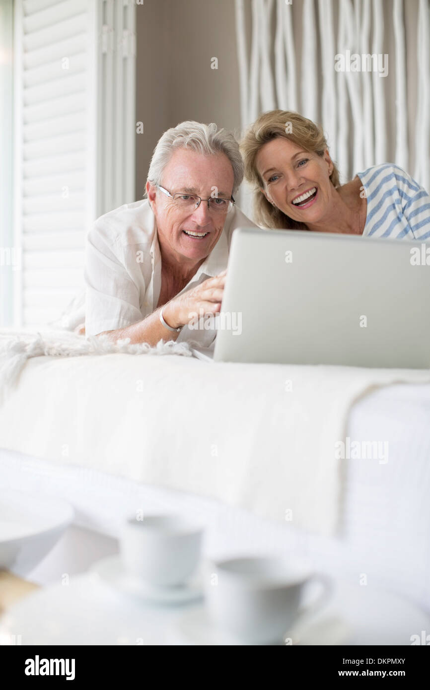 Older couple using laptop on bed - Stock Image