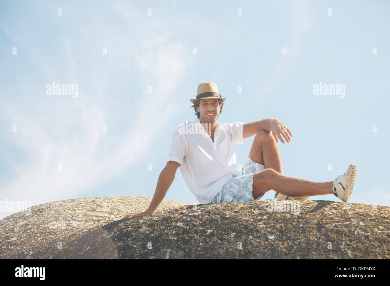 Man sitting on rock formation - Stock Image