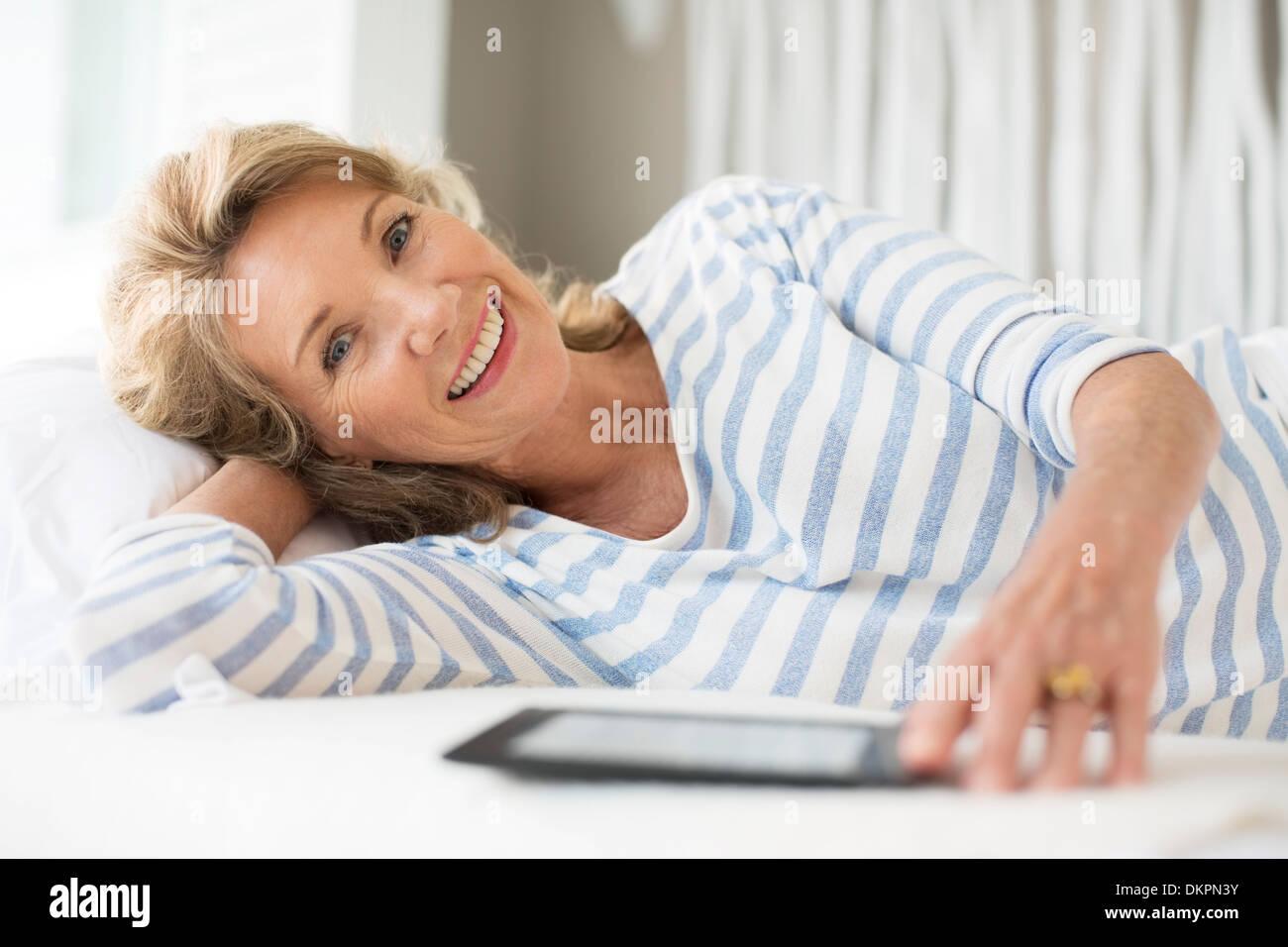Older woman using digital tablet on bed - Stock Image