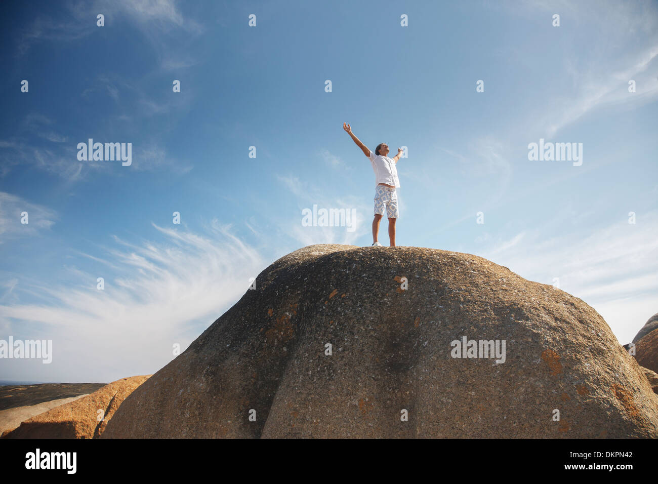 Man standing on top of rock formation - Stock Image