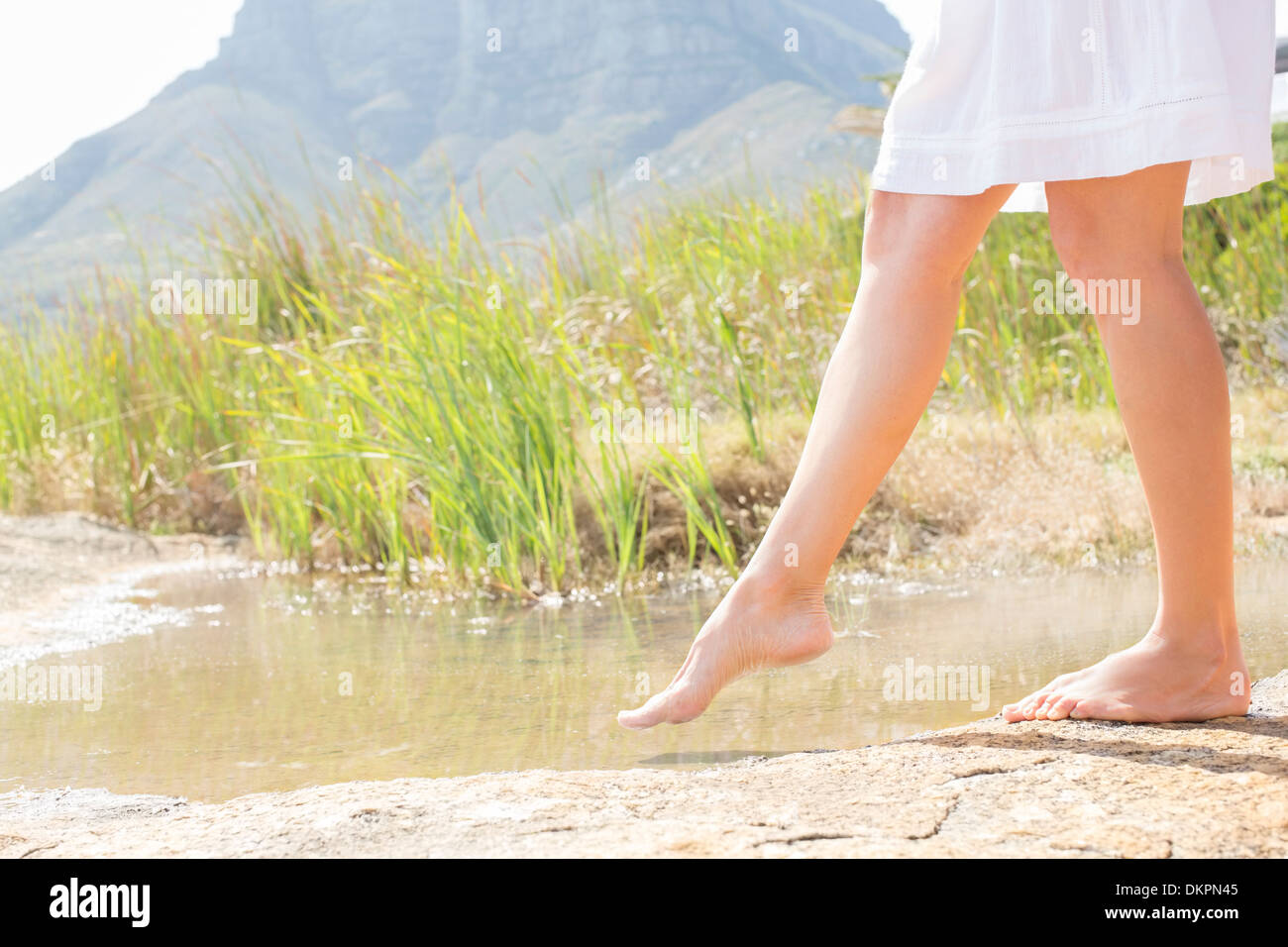 Woman dipping toe in rural pond - Stock Image