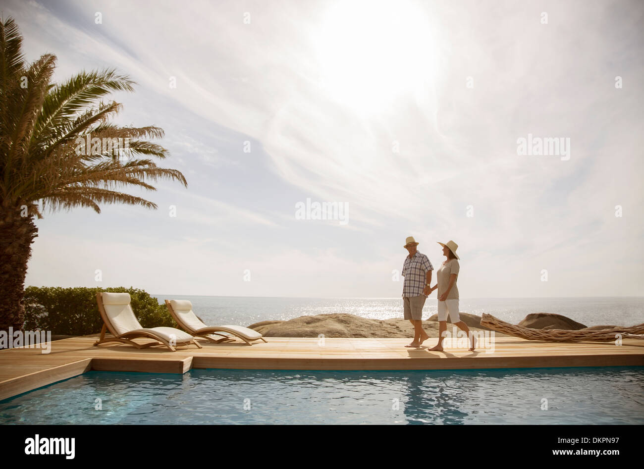 Older couple relaxing together by pool - Stock Image