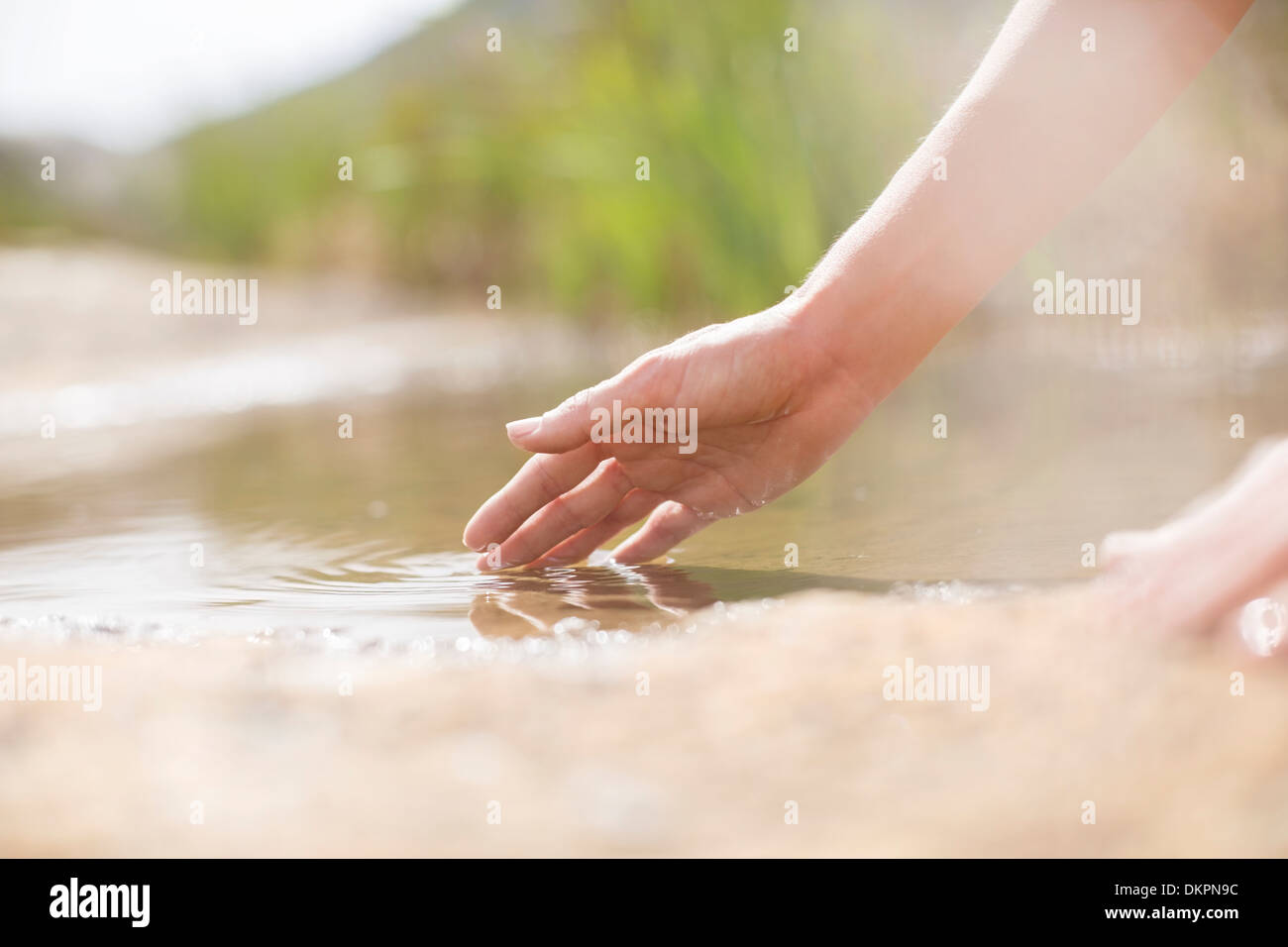 Woman dipping fingers in rural pond - Stock Image