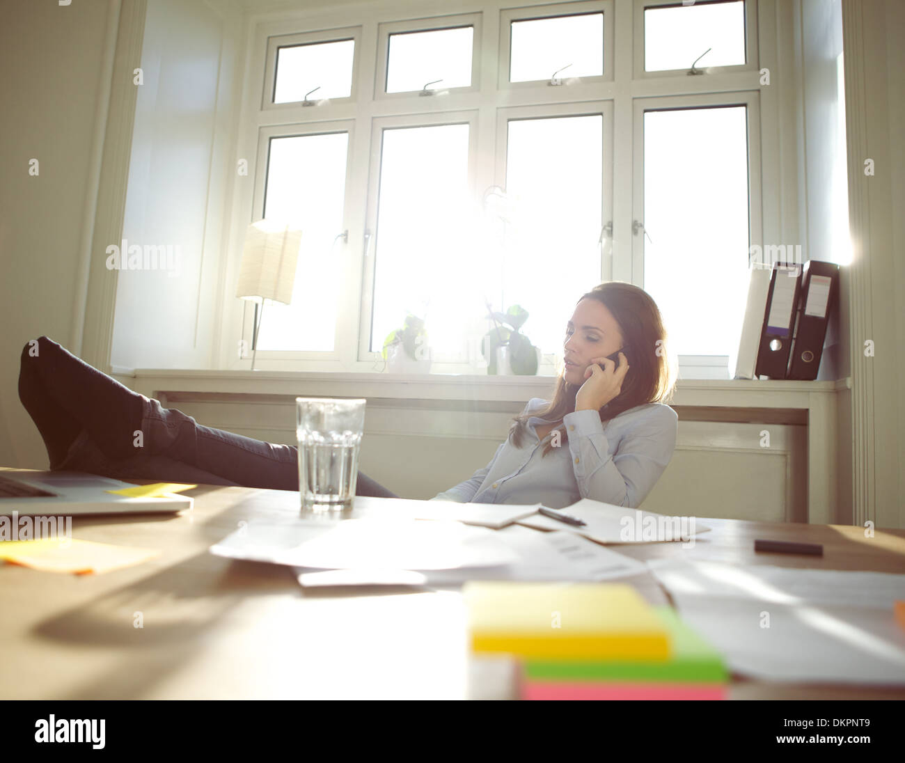 Young woman sitting at her table with legs on desk talking on mobile phone. Caucasian businesswoman using cell phone. Stock Photo