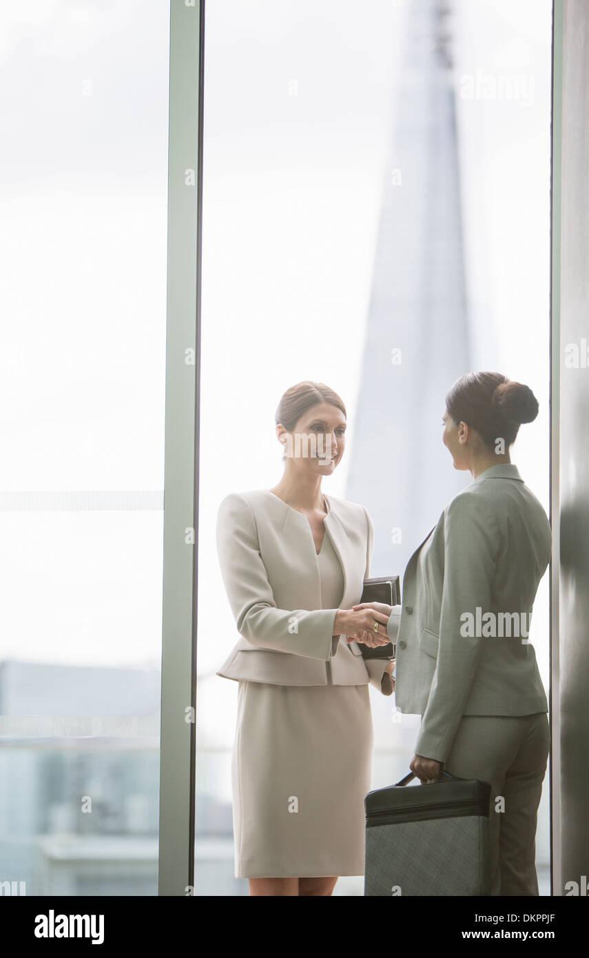 Businesswomen shaking hands in office - Stock Image