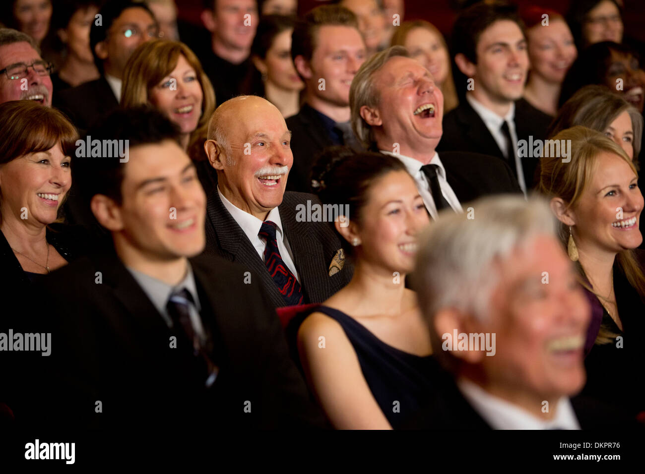 People smiling and laughing in theater audience - Stock Image