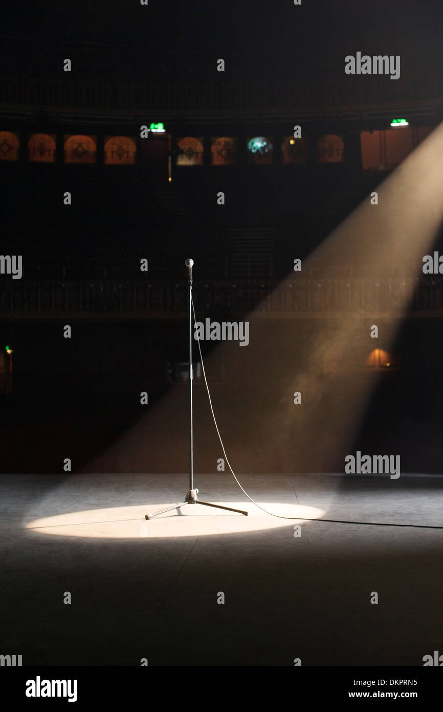 Microphone in spotlight on empty theater stage - Stock Image