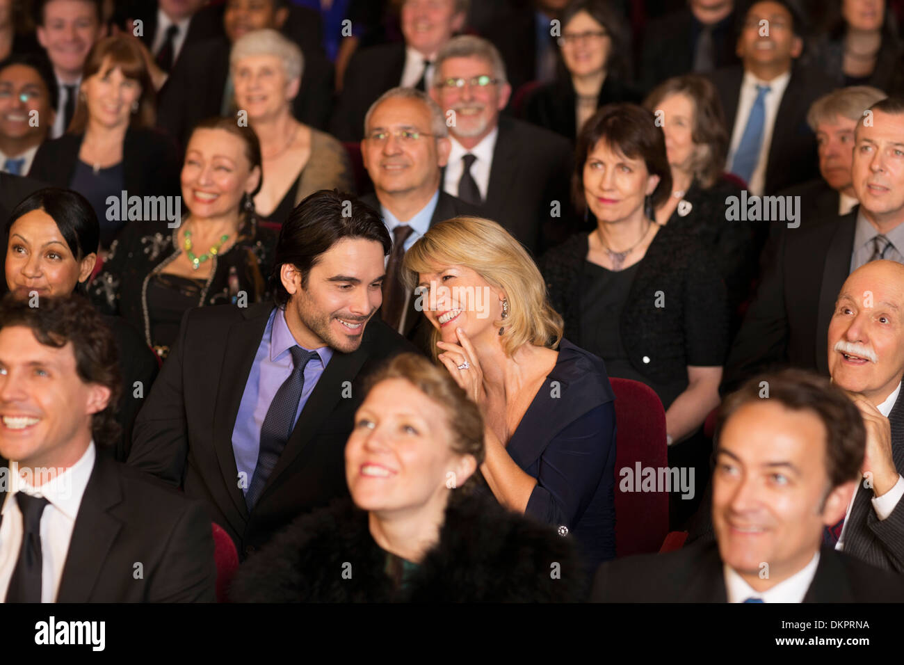 Happy couple clapping in theater audience - Stock Image