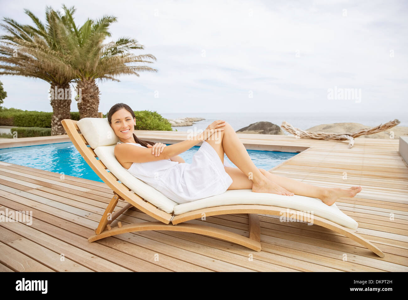 Woman relaxing in lounge chair at poolside Stock Photo