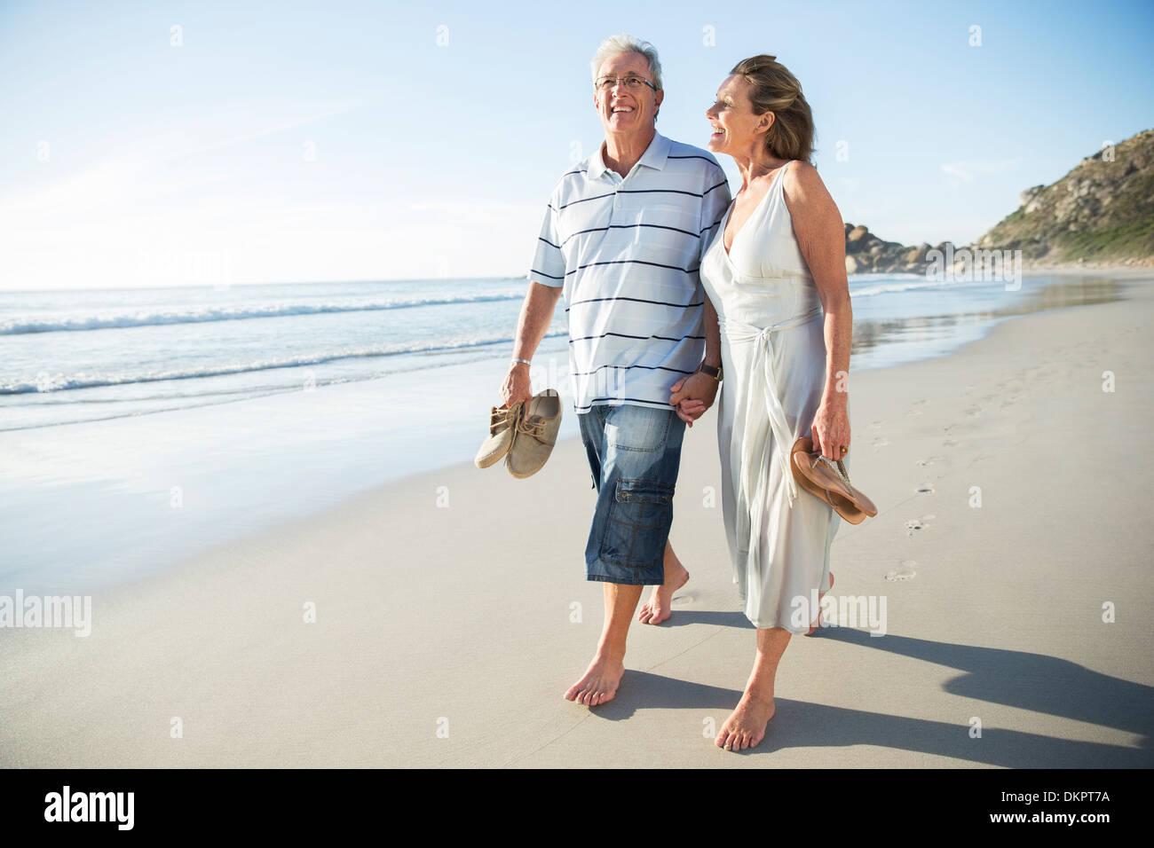 Senior couple walking on beach - Stock Image