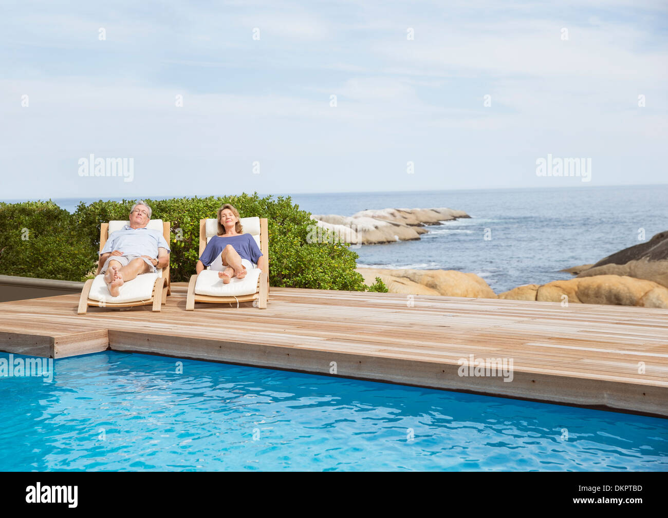 Senior couple relaxing at poolside Stock Photo