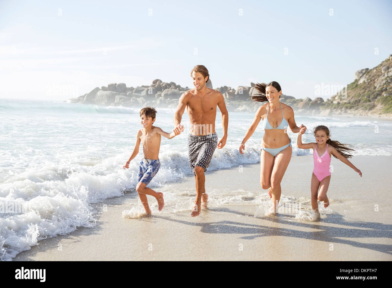 Family running together in waves - Stock Image